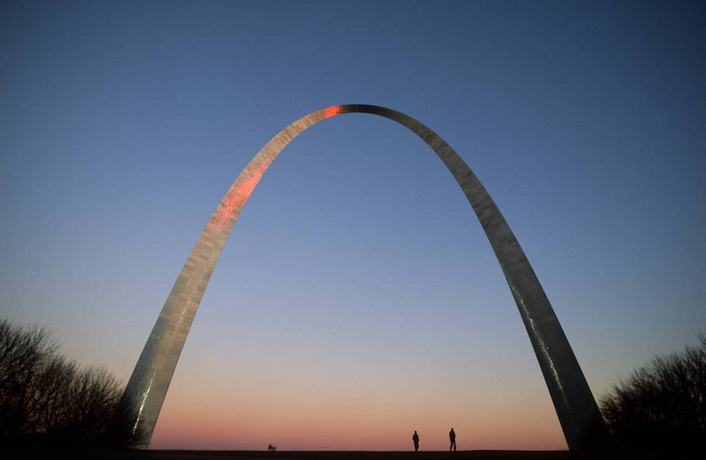 Photo: Two people walk under the St. Louis Arch.