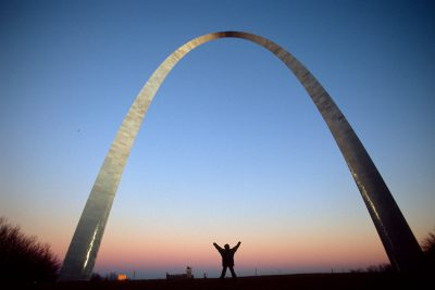 Photo: A person raises his hands underneath the St. Louis Arch.