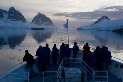 Photo: Tourists along the bow of a cruise boat in the Antarctic Peninsula.