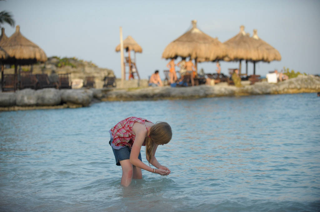 Photo: A girl sifts through the sand at the Xcaret resort in Cancun, Mexico.