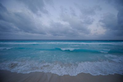 Photo: The Caribbean Sea laps on the shore of Mar Caribe peninsula, Cancun, Mexico.