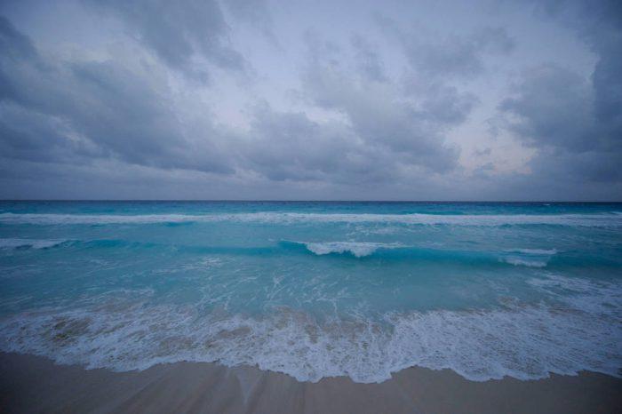 Photo: The Caribbean Sea laps on the shore of Mar Caribe peninsula, Cancun, Mexico.