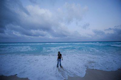 Photo: A twelve year-old girl walks along the shores of Mar Caribe peninsula, Cancun, Mexico.