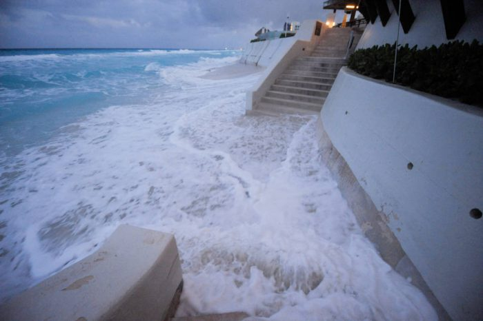 Photo: Waves lap up against the base of the Me by Melia Hotel in Cancun, Mexico.