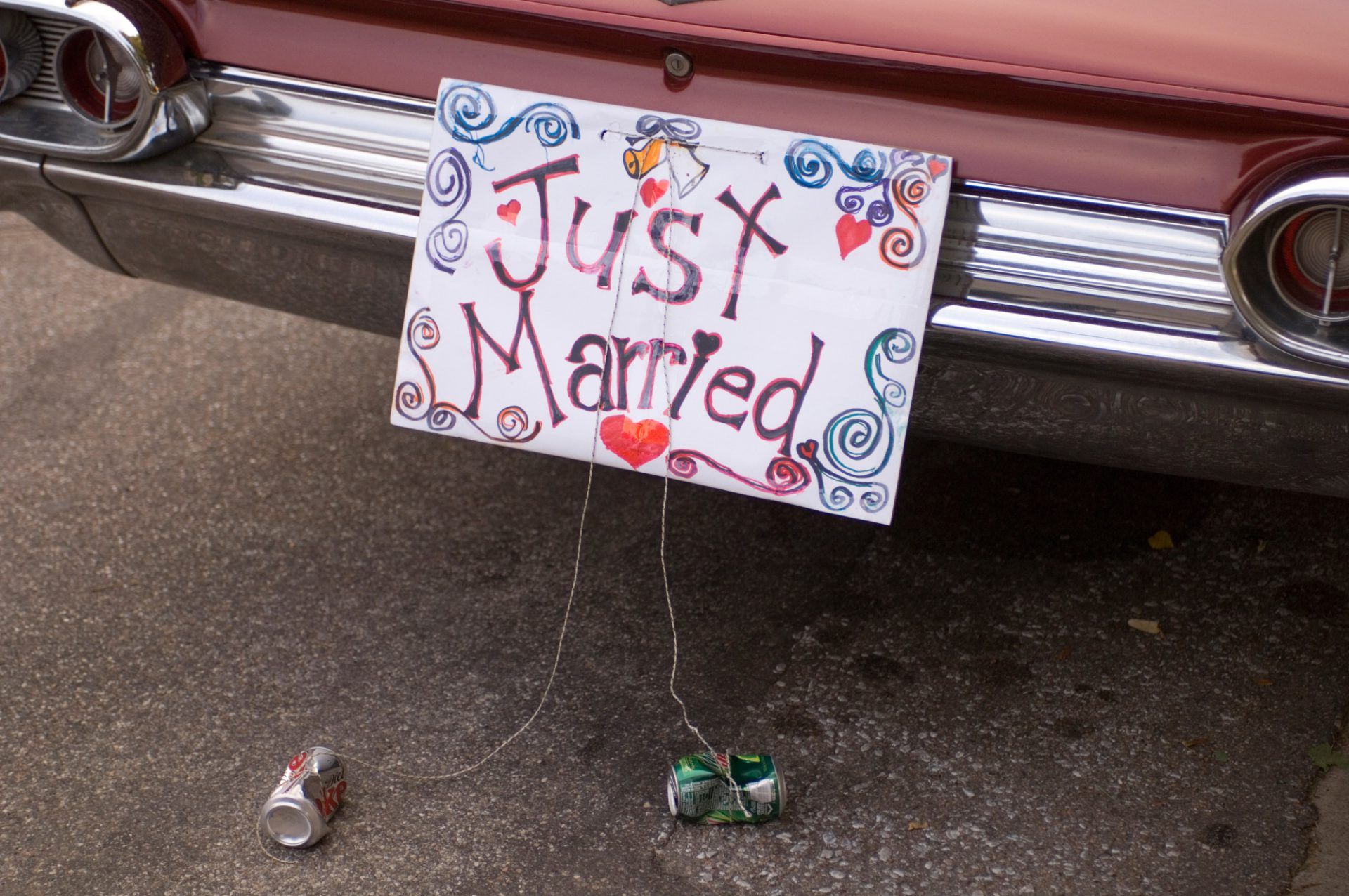 Photo: A hand made sign hangs from a bride and groom's get-away car.