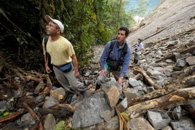 Photo: Two scientists examine a ravine demolished by a road-widening/gravel mining project in Ecuador.