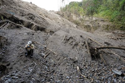 Photo: A researcher surveys a ravine that was clogged by a road-widening/gravel mining project near Limon, Ecuador.