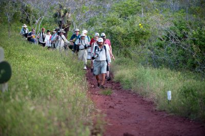 Photo: A group of tourists venture along a walking trail on Rabida Island in Galapagos National Park.