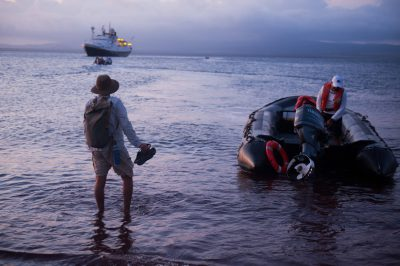 Photo: A Galapagos guide, prepares to leave the island of Rabida in Galapagos National Park.