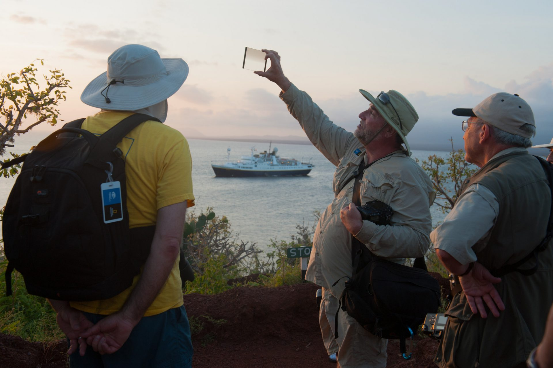 Photo: A nuetral density filter is explained to photography-interested guests on Rabida Island in Galapagos National Park.