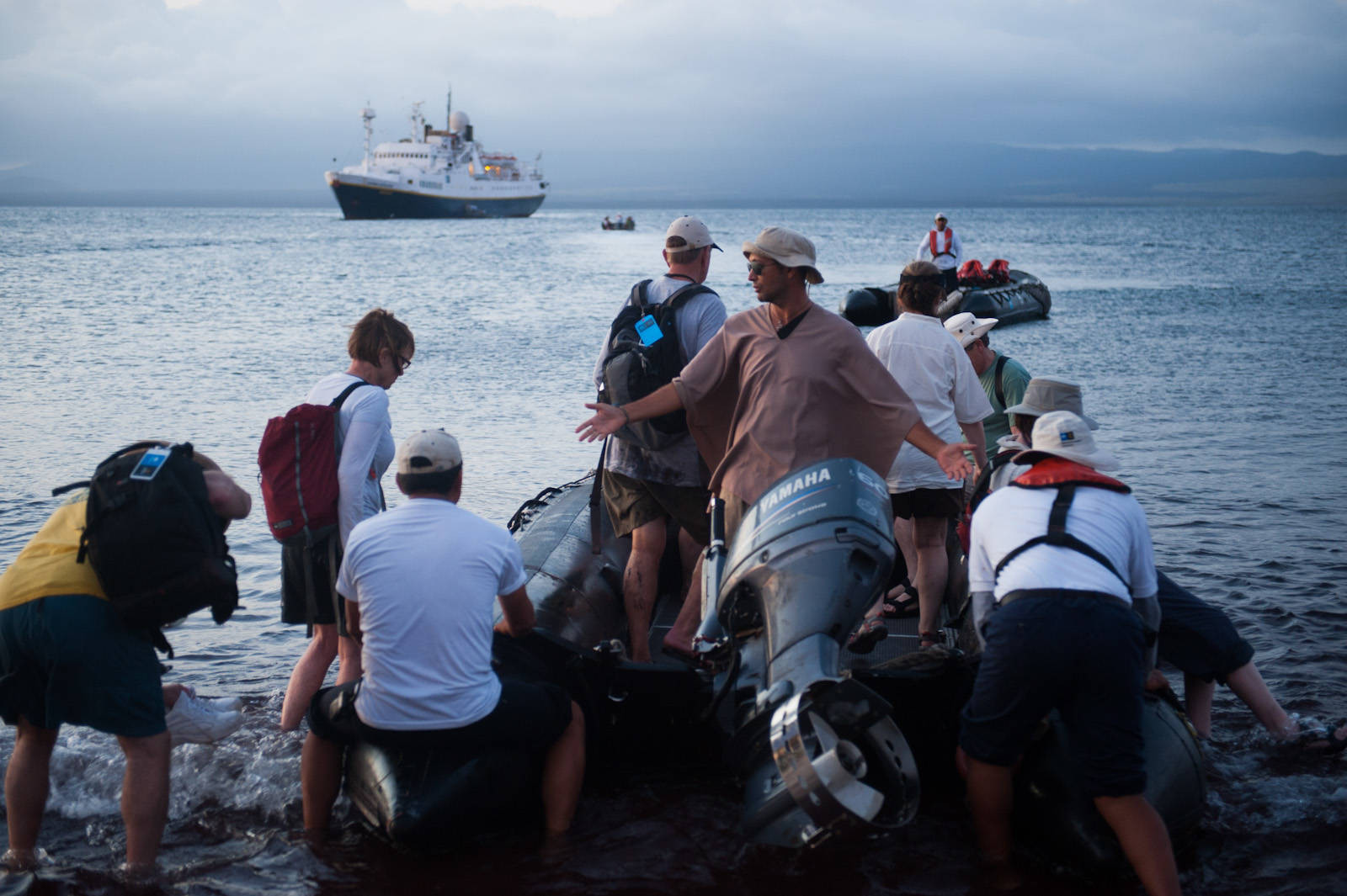 Photo: A guide encourages tourists to get on board a zodiac loading at day's end on Rabida Island in Galapagos National Park.