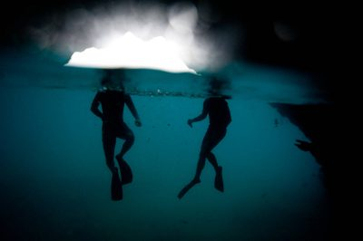 Photo: Two swimmers surface in the water close to Santiago Island in Galapagos National Park.