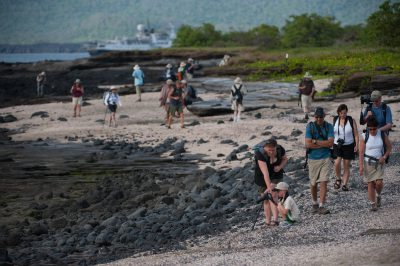 Photo: Tourist walk along the beach along Puerto Egas, Santiago Island in Galapagos National Park.