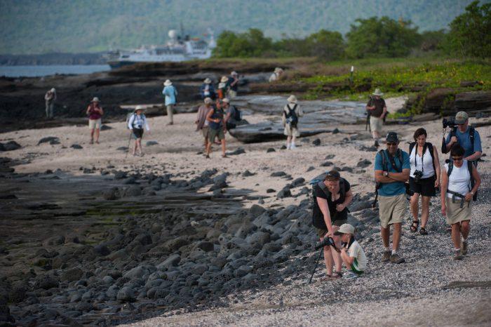 Photo: Tourist walk along the beach along Puerto Egas, Santiago Island in Galapagos National Park.
