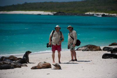 Photo: Two photographers search for photo opportunities among the Galapagos sea lions (Zalophus wollebaeki) on Espanola Island in Galapagos National Park.