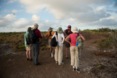 Photo: Tourists stop to watch the birds on Tower Island in Galapagos National Park.