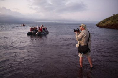 Photo: A man photographs tourists departing from Rabida Island in Galapagos National Park.
