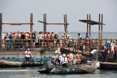 Photo: Tourists board zodiac boats on San Cristobal Island in the Galapagos.