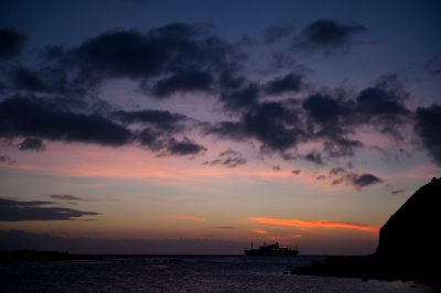 Photo: Silhouette of a cruise ship at sunset near San Cristobal Island in the Galapagos.
