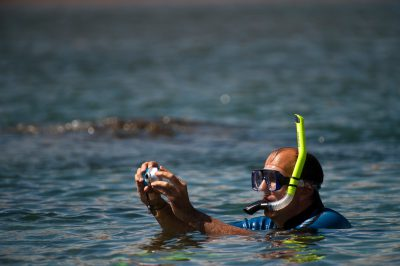 Photo: A tourist photographs the scenary around him while snorkeling in the Galapagos.