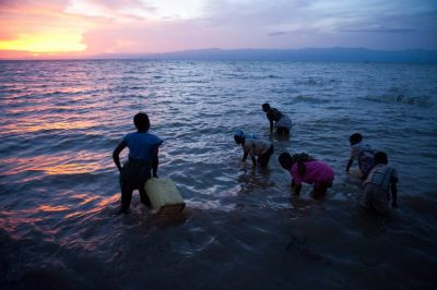 Photo: At the fishing village of Kyehoro residents dunk gerry cans at dusk in Lake Albert to gather dirty water to drink.