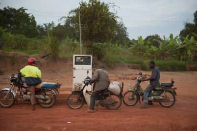 Photo: Three men fuel up their motorcycles in Uganda, Africa.