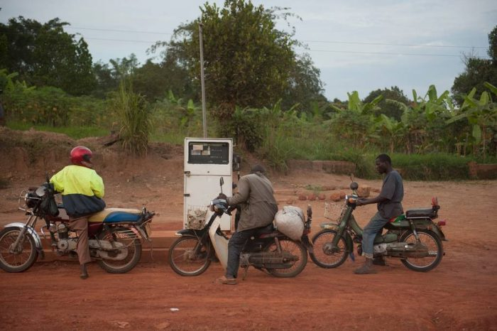 Photo: Three men fuel up their motorcycles in Uganda, Africa.