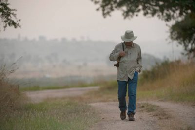 Photo: A man walks through Queen Elizabeth National Park in Uganda, Africa.