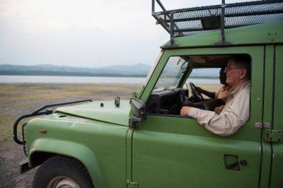 Photo: Two men drive through the Mweya area of Uganda, Africa.