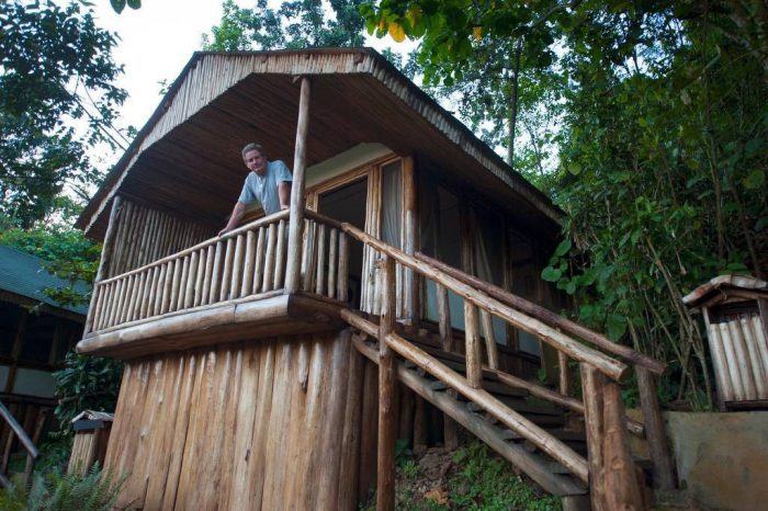 Photo: A man stands on the porch of his cabin at Bahoma Lodge, near Bwindi Impenetrable Forest National Park in Uganda, Africa.