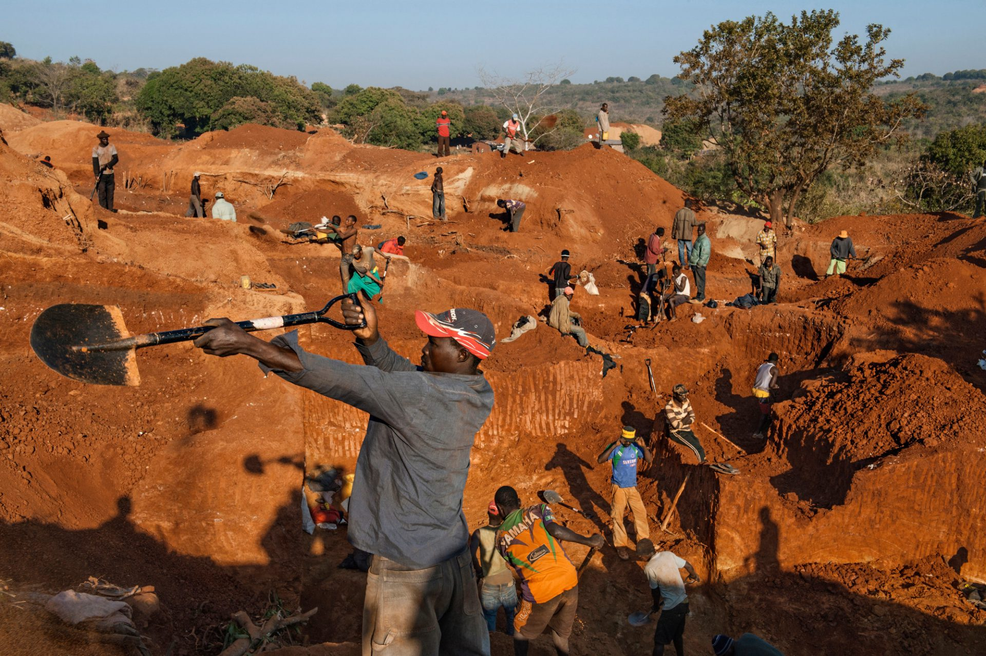 Photo: Teams of miners with a government permit dig for gold.