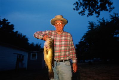 Photo: A man holds up his catch of the day from an Arma, Kansas fishing hole.
