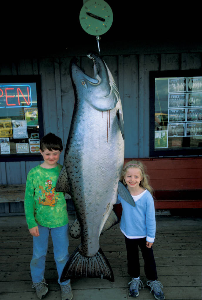 Photo: Cole and Ellen Sartore next to a very large -- and very fake -- king salmon in front of a store in Homer, Alaska (on the Kenai River).