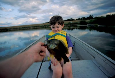 Photo: Cole Sartore warily eyes his father's catch as they fish on a farm pond in Nebraska.