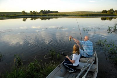 Photo: An older man goes fishing for largemouth bass with his granddaughter at a Nebraska farm pond.