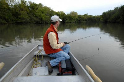 Photo: A man goes bass fishing on a strip mining pit in Southeast KS.