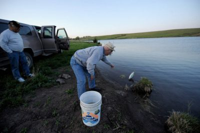 Photo: A senior man goes catch-and-release fishing on a Nebraska farm pond.