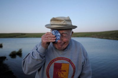 Photo: A senior man wipes his forehead on a fishing trip at a Nebraska farm pond.