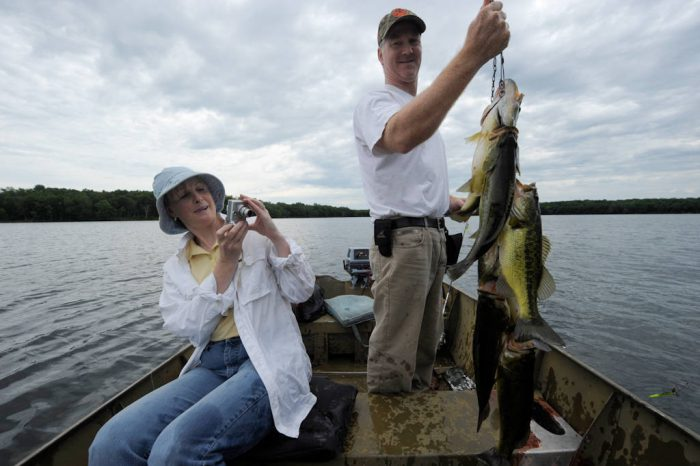 Photo: A man proudly displays the fish he caught with his sister-in-law at Crosslake, Minnesota.