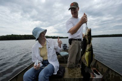 Photo: A man gets a thumbs up from his sister-in-law as he proudly shows off his catch of fish at Crosslake, Minnesota.