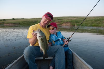 Photo: A father and son inspect their catch, a large mouth bass, Valparaiso, Nebraska.