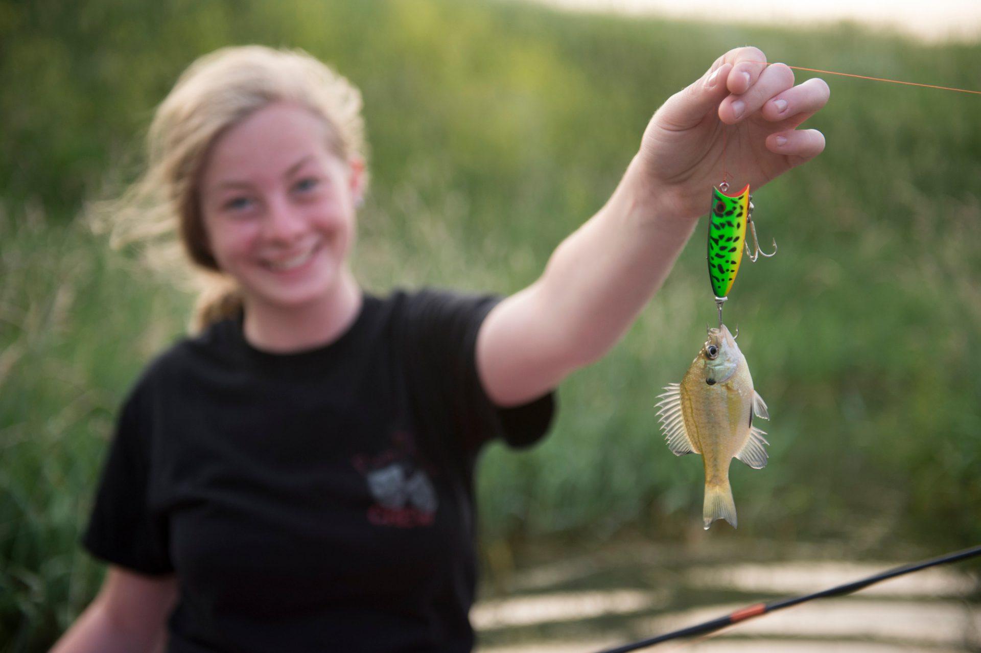 Photo: A teenage girl holds up her tiny catch, Loma, Nebraska.