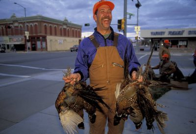 Photo: A successful hunter holds his game after the One Box Pheasant Hunt in Broken Bow, Nebraska.
