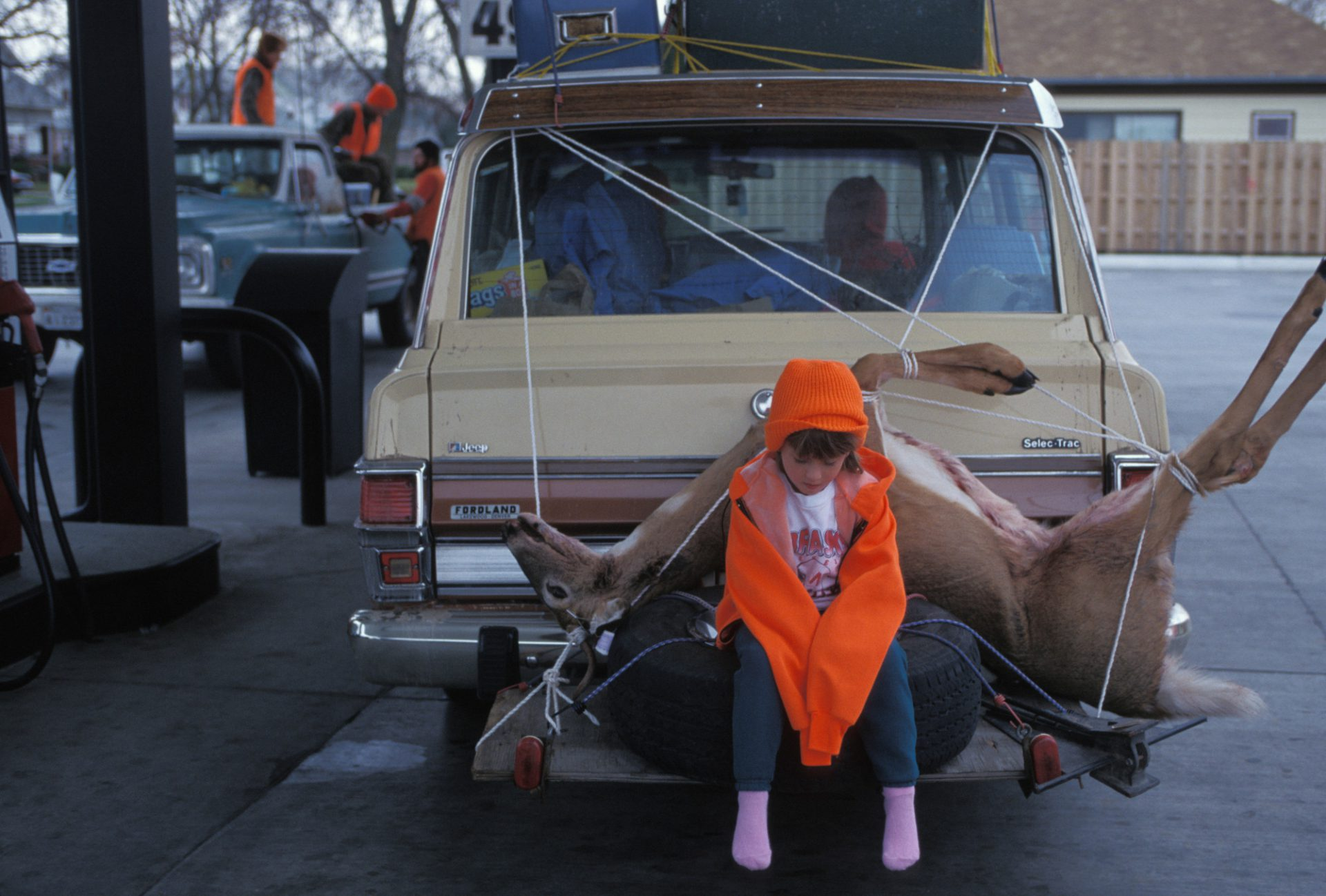 Photo: A young girl waits near a dead deer at a gas station in Broken Bow, Nebraska.