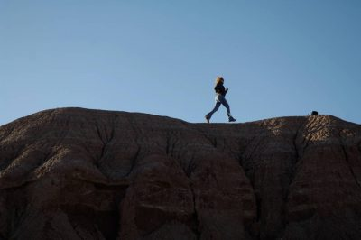 Photo: A woman walks past a rock outcropping at Ghost Ranch near Santa Fe.