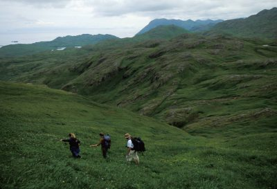 Photo: Three people climp to the top of Mt. Reed on Adak Island, Alaska.