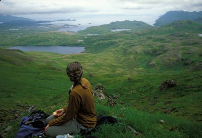 Photo: A woman stops for lunch while climbing to the top of Mount Reed on Adak Island, Alaska.