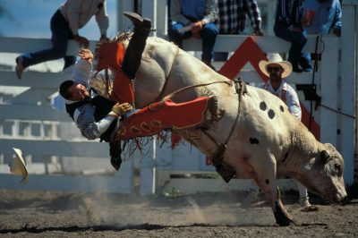 Photo: A bull rider is knocked from his mount as a rodeo clown looks on at Nebraska's Big Rodeo in Burwell.