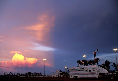 Photo: The sky splits in half as a showman performs at Nebraska's Big Rodeo in Burwell.