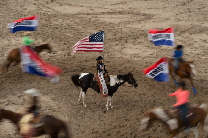 Photo: Rodeo queens on horses circle a rodeo queen who is holding the American flag.